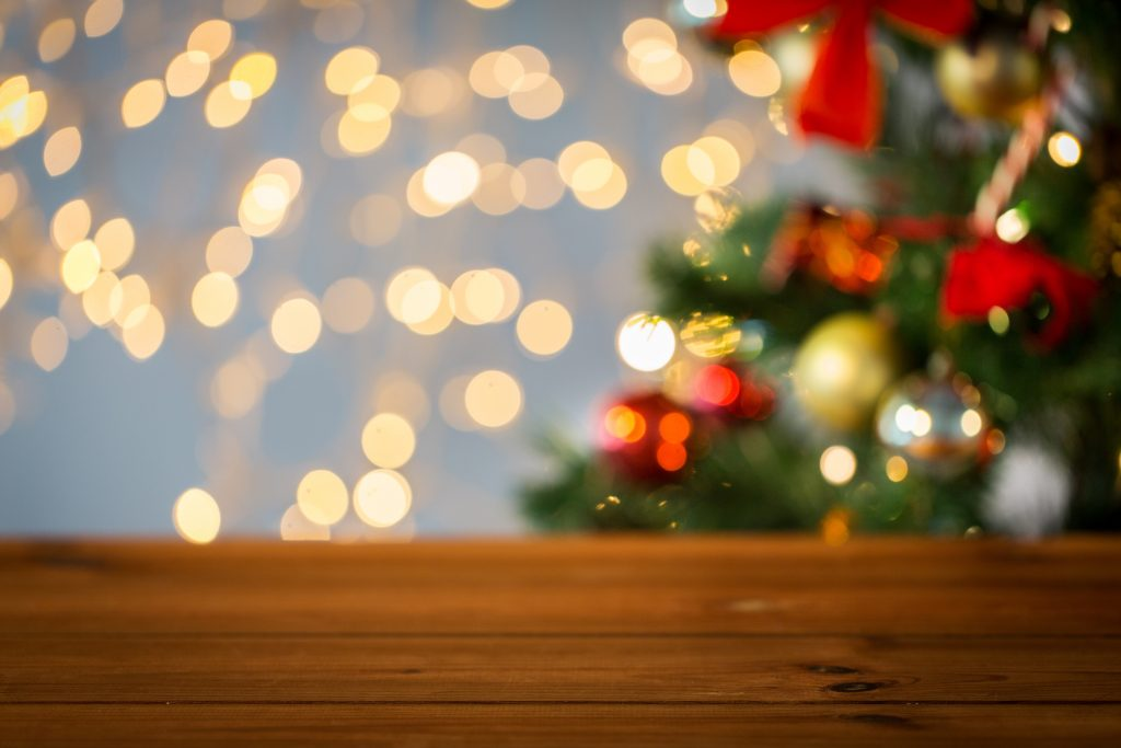 christmas tree and lights in background with wooden table in foreground