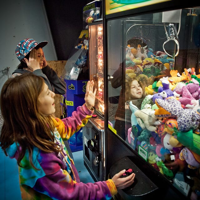 kids playing a claw machine at the arcade