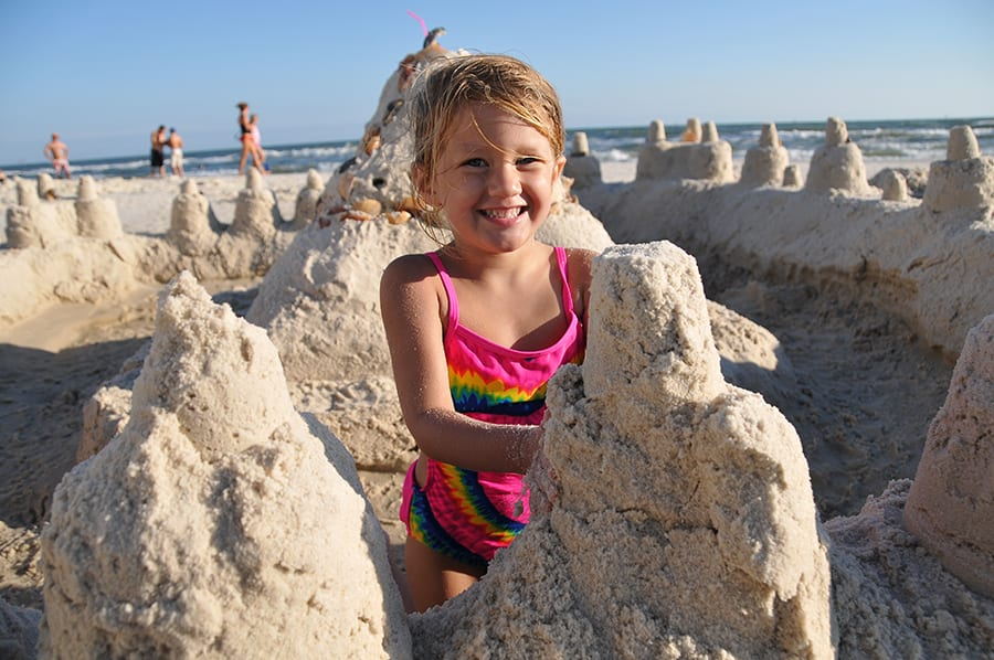 little girl building sandcastles on the beach